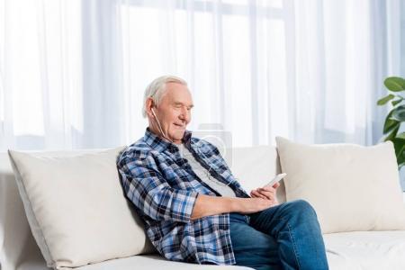 Foto de Vista lateral del sonriente hombre senior auriculares smartphone descansando en el sofá en casa - Imagen libre de derechos