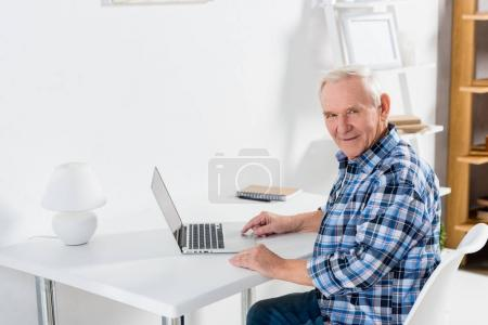 side view of senior man sitting at table with laptop and looking at camera at home
