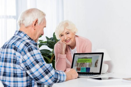 Photo for Portrait of senior wife looking at husband using laptop with bbc logo at home - Royalty Free Image
