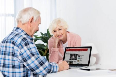 portrait of cheerful senior woman looking at husband using laptop with bbc logo at home