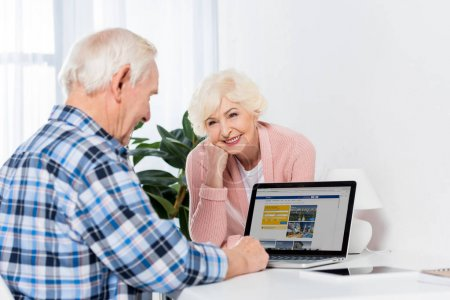 portrait of senior wife looking at husband using laptop with booking logo at home