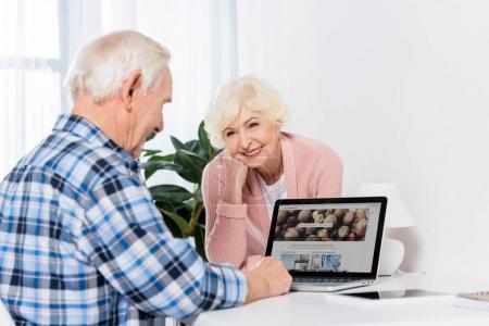 Photo pour Portrait de femme senior regardant mari travaillant sur ordinateur portable avec le logo de depositphotos à la maison - image libre de droit