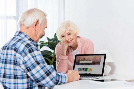 portrait of happy senior woman looking at husband using laptop at home