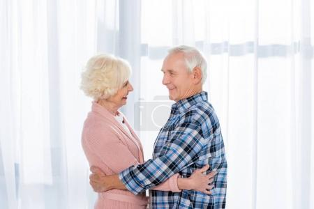 side view of cheerful senior couple hugging and looking at each other