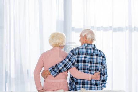 beautiful senior couple embracing in front of window