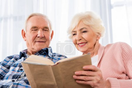 happy senior couple reading book together