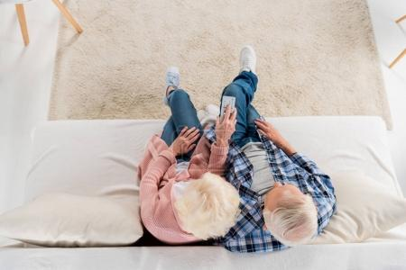 top view of senior couple with remote control watching tv on couch