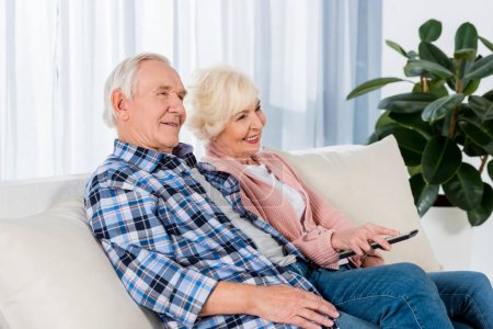 Photo for Happy senior couple with remote control watching tv on couch - Royalty Free Image