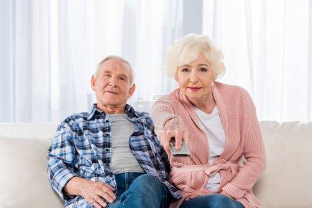 Photo pour Couple aîné avec télécommande regarder la télévision sur le canapé - image libre de droit