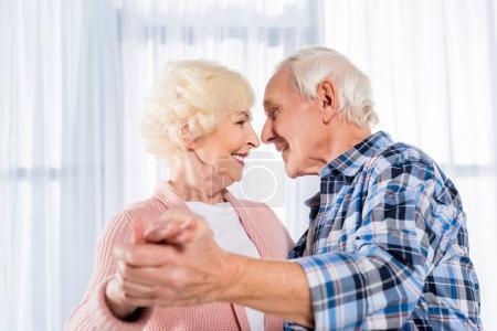 Photo pour Vue latérale d'un couple de personnes âgées souriant dansant ensemble à la maison - image libre de droit