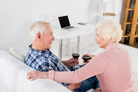 back view of senior man and woman with glasses of red wine looking at each other at home