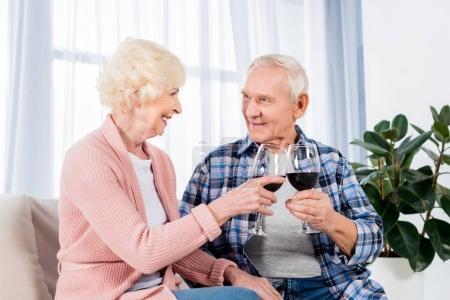 Photo pour Portrait de verres tintements heureux couple de personnes âgées d'un vin rouge tout en reposant sur le sofa à la maison - image libre de droit
