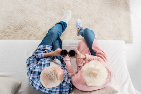 overhead view of senior couple with glasses of red wine resting on sofa at home