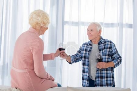 side view of senior man giving glass of red wine to wife at home
