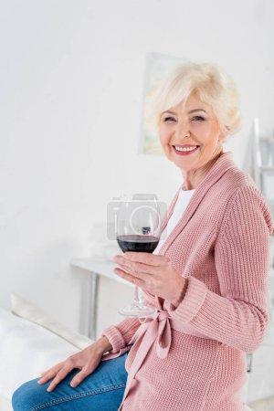 Portrait de la belle femme senior heureuse avec verre de vin rouge à la maison
