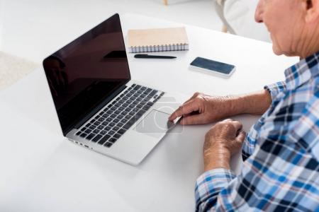 partial view of senior man working on laptop with blank screen at table with notebook at home