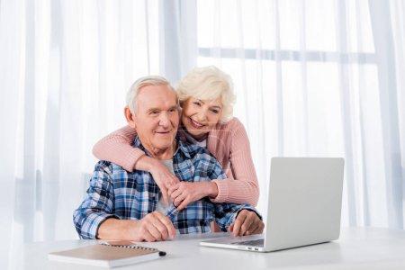 Photo pour Portrait de joyeux couple de personnes âgées utilisant un ordinateur portable ensemble à la maison - image libre de droit