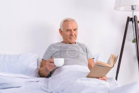 portrait of senior man with cup of coffee reading book in bed at home
