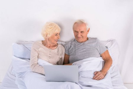 senior couple using laptop while resting in bed at home