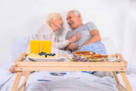 selective focus of breakfast and happy senior couple in bed at home