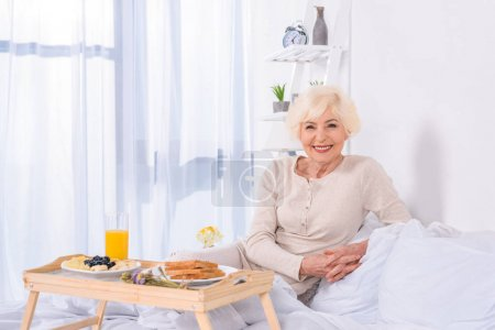portrait of happy senior woman with breakfast in bed looking at camera at home