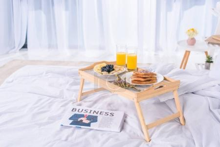healthy breakfast in bed on wooden tray at morning