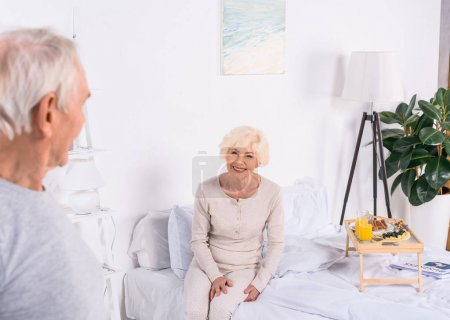 happy senior woman sitting on bed and looking at husband at home