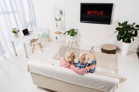 senior couple watching netflix on tv at home