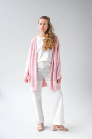 confident girl in trendy clothes standing and looking away on white