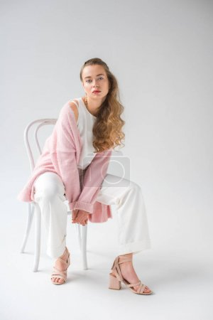 Photo for Fashionable girl sitting on wooden chair and looking at camera on white - Royalty Free Image