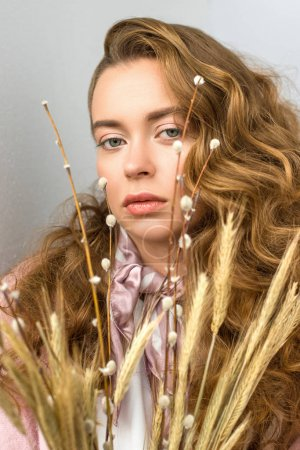portrait of woman with curly hair with willow tree branches and spikelets on foreground