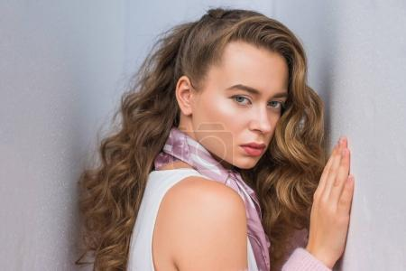 attractive girl with curly hair leaning on gray wall and posing for fashion shoot