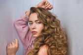 fashionable woman with curly hair posing for fashion shoot between gray walls