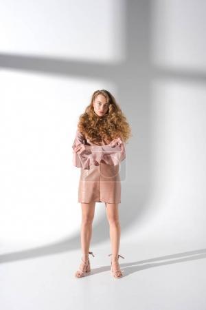 Photo pour Sceptique belle fille debout avec les mains croisées et regardant caméra - image libre de droit