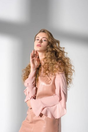 beautiful woman in beige dress touching neck with hand