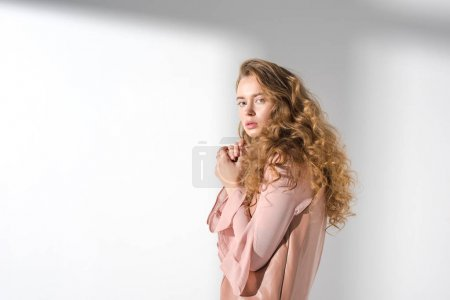 confused girl in beige dress with curly hair looking at camera