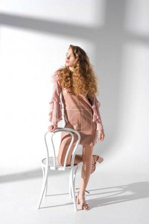 belle jeune fille en robe beige s'appuyant sur une chaise avec un genou et à la recherche.