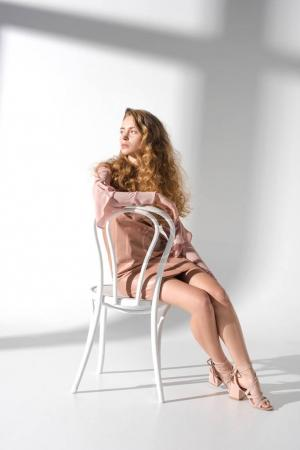 fashionable woman in beige dress and curly hair sitting on white chair