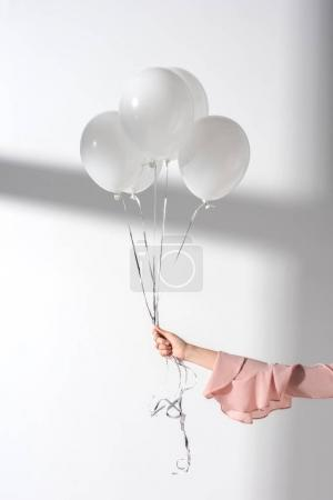 Photo for Cropped image of girl holding bundle of balloons with helium in hand - Royalty Free Image