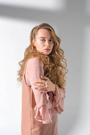 confident girl with curly hair standing and posing for fashion shoot