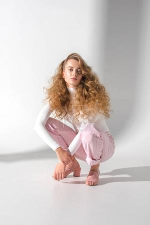 beautiful girl with curly hair squatting and looking at camera