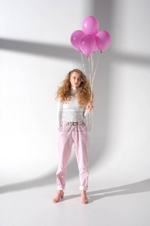 serious girl in stylish outfit standing with pink balloons with helium