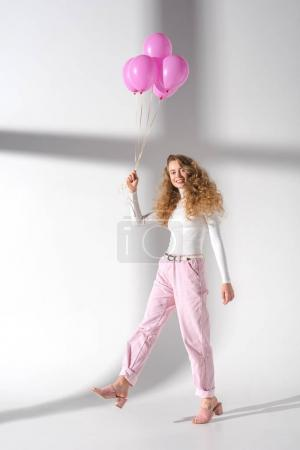 smiling woman going with bundle of pink balloons
