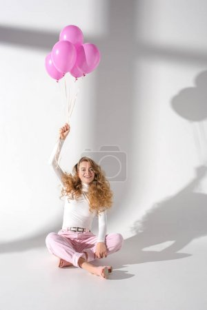 happy beautiful girl with hand up sitting and holding bundle of balloons