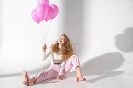 smiling girl with bundle of pink balloons sitting and looking up