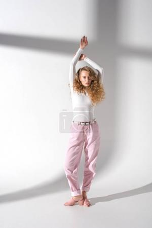 attractive girl with curly hair standing with hands up and looking at camera
