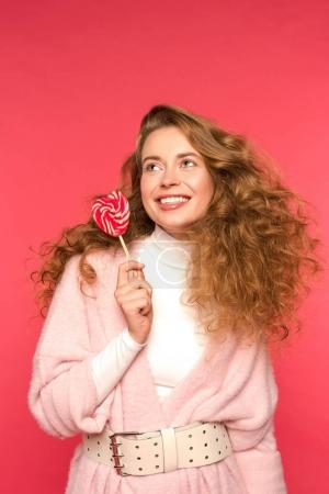 smiling girl holding heart shaped lollipop isolated on red