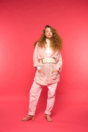 Photo for Serious stylish girl in pink outfit looking at camera isolated on red - Royalty Free Image