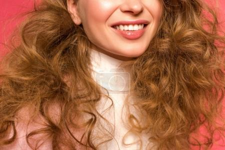 Cropped image of smiling girl with curly hair on red