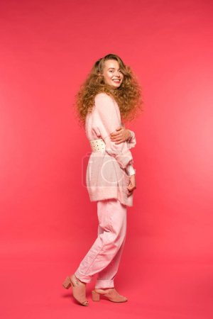 stylish smiling girl standing in pink clothes and looking at camera isolated on red
